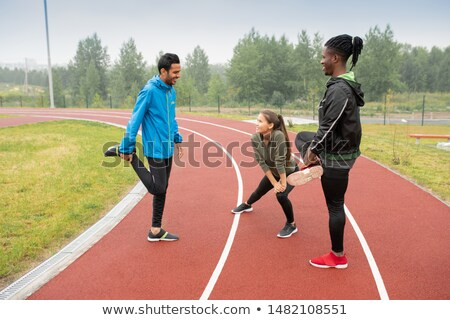 Group of young intercultural athletes doing wam-up exercises on racetracks Stock photo © pressmaster