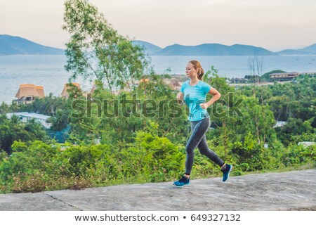 A sportive young woman is engaged in running against the sea Stock photo © galitskaya
