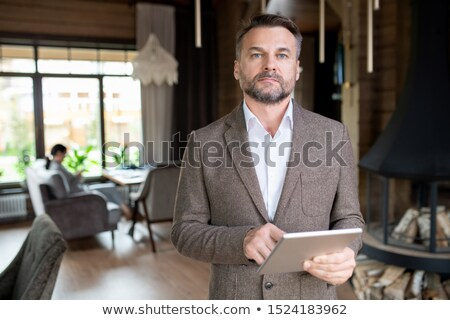 serious middle aged businessman with beard scrolling in touchpad in restaurant stock photo © pressmaster