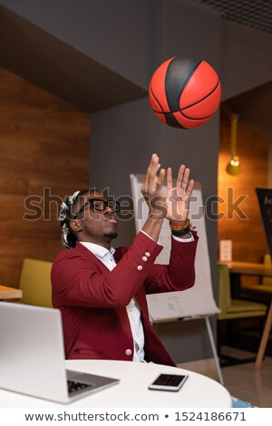 african guy throwing ball upwards while sitting by table in modern cafe stock photo © pressmaster