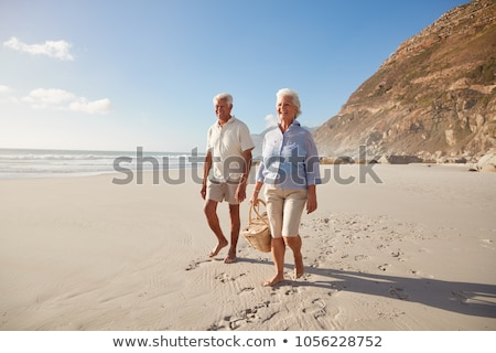 Front view of happy senior couple holding hands and walking on beach in the sunshine Stock photo © wavebreak_media