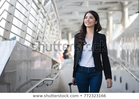 Happy young successful female business traveler with luggage looking at you Stock photo © pressmaster