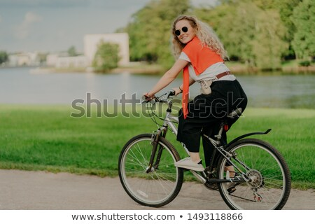 Image of female model rides bicycle, looks aside with cheerful expression, wears sunglasses, breathe Stock photo © vkstudio