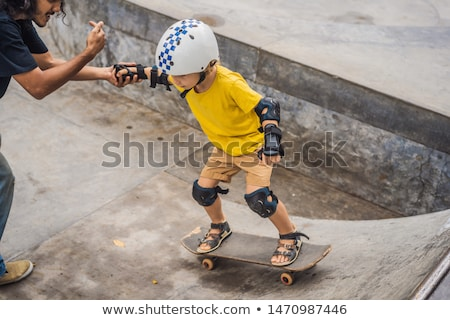 Athletic boy learns to skateboard with a trainer in a skate park. Children education, sports BANNER, Stock photo © galitskaya