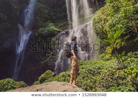 Man in turquoise dress at the Sekumpul waterfalls in jungles on Bali island, Indonesia. Bali Travel  Stock photo © galitskaya