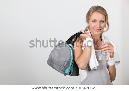 Blond woman wearing sportswear holding water bottle with bag over shoulder Stock photo © photography33