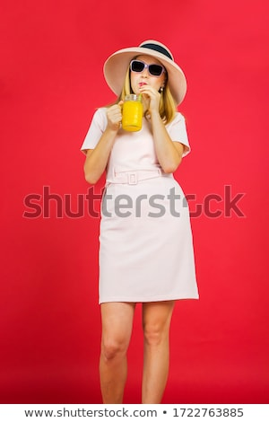 Gorgeous red-haired female drinking a glass of orange juice while sitting on her bed stock photo © wavebreak_media