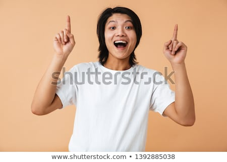 happy casual man pointing upwards over white background stock photo © deandrobot