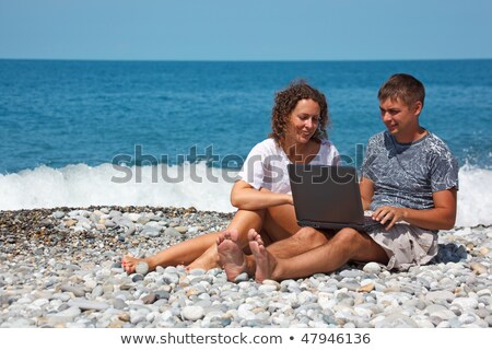 Man and girl sitting on seashore. With interest in looking at laptop standing on their knees. Close- Stock photo © Paha_L