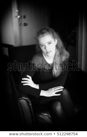 Gorgeous thoughtful woman in black dress sitting on leather sofa  Stock photo © deandrobot