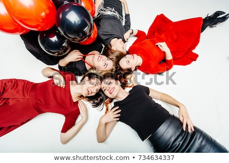 Relaxed woman in black dress lying on sparkling background Stock photo © deandrobot