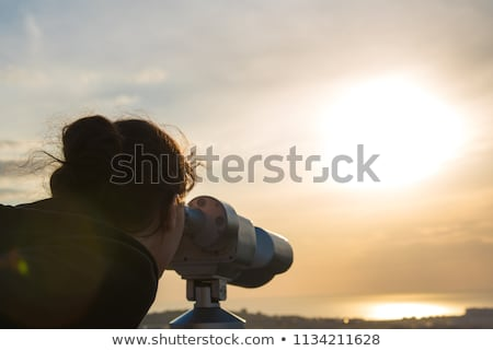 Girl looking through a telescope at the panorama of the city Stock photo © vlad_star