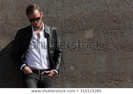 Moda homem jaqueta de couro óculos de sol olhando para baixo branco Foto stock © feedough