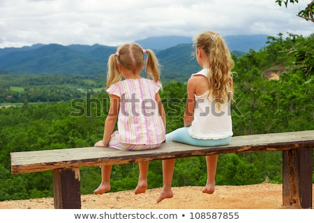 Beautiful sad girl sits on bench against summer nature. stock photo © konradbak