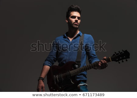 young dramatic guitarist looking away to side while playing stock photo © feedough