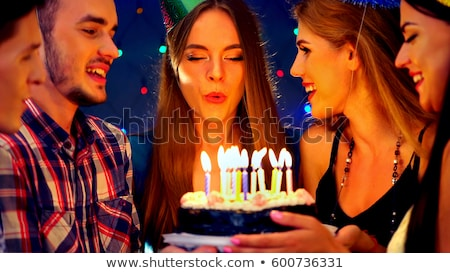Young girl wearing party hat with birthday cake smiling Stock photo © monkey_business