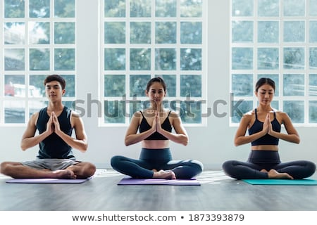 Full-length image of Young fitness woman warming up in studio Stock photo © deandrobot
