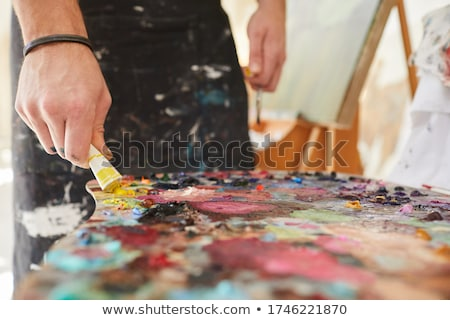 artist with palette painting at art studio Stock photo © dolgachov