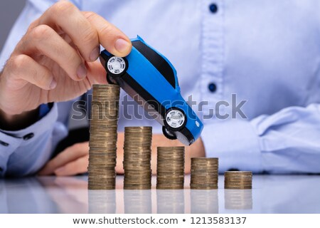 Person's Hand Driving Car On Decreasing Stacked Coins Stock photo © AndreyPopov