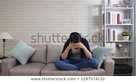 sad girl sitting on sofa stock photo © andreypopov