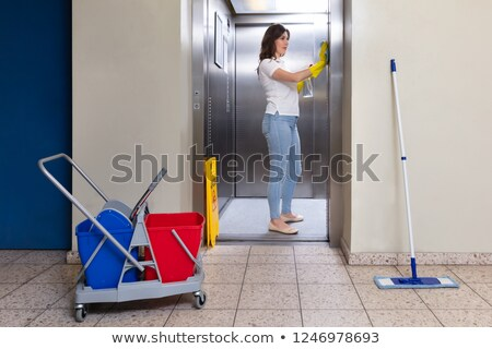 Female Janitor Wearing Gloves Cleaning Elevator Stock photo © AndreyPopov