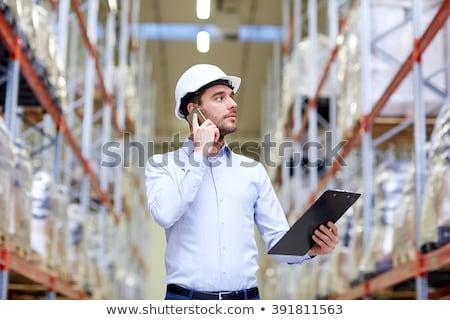 businessman calling on smartphone at warehouse Stock photo © dolgachov
