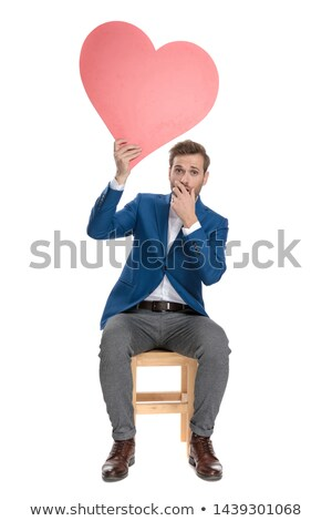 man holding a red heart on hand while looking amazed Stock photo © feedough