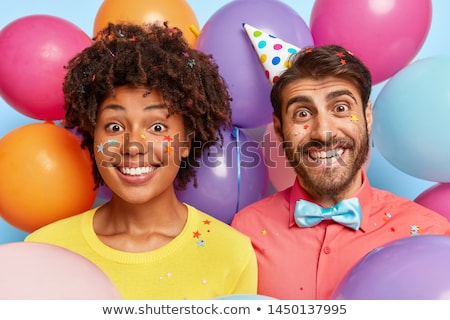 happy couple in party hats with balloons stock photo © dolgachov