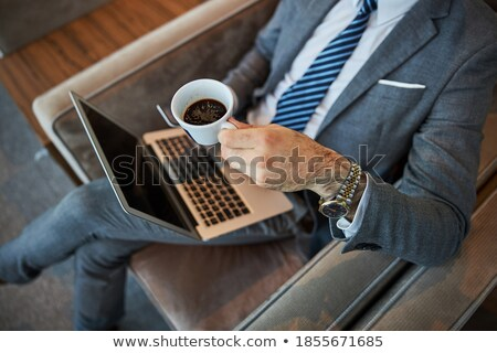 Cropped image from above of caucasian businessman sitting at tab Stock photo © deandrobot