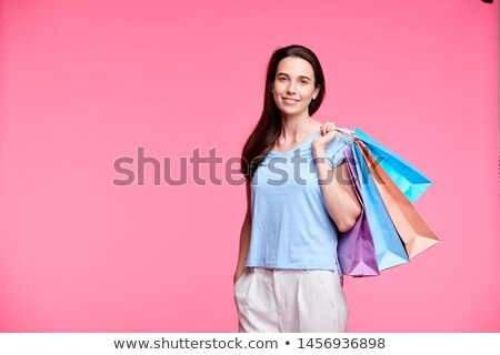 Young pretty shopaholic with shoppng bags Stock photo © pressmaster