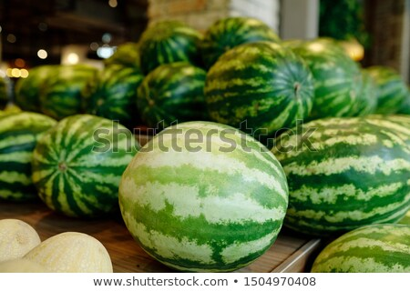 Pile of green large watermelons lying on wooden display Stock photo © pressmaster