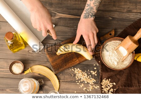 banana prepared for cutting on a wooden board for cutting and fruits around stock photo © galitskaya