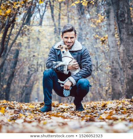 Young man walking his dog having a stroll in the autumn park Stock photo © Kzenon
