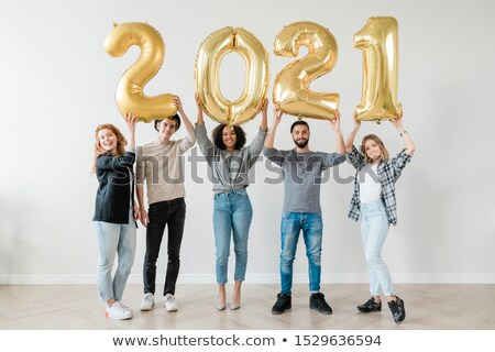 cheerful guys and girls holding number of new year in raised hands stock photo © pressmaster