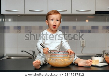 Cute blond boy using whisker while mixing flour and eggs in steel bowl Stock photo © pressmaster