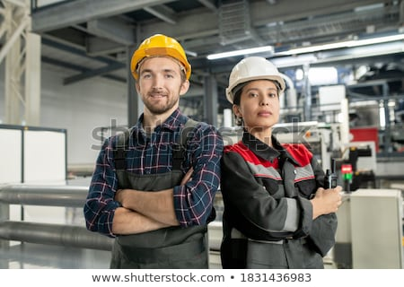 Young engineer or foreman in protective helmet and workwear using digital tablet Stock photo © pressmaster