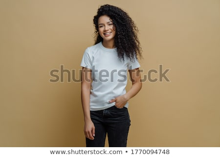 Photo of smiling woman with curly dark hair, has slim figure, wears white t shirt and black jeans, h Stock photo © vkstudio