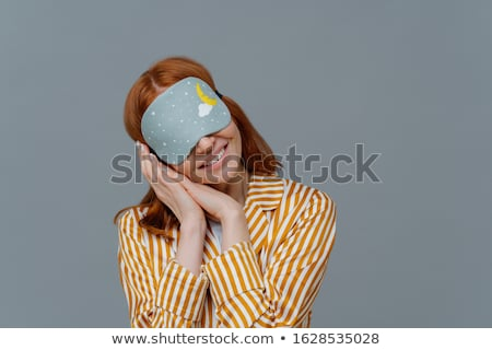 Just relaxing or time for nap. Smiling gentle woman with eye mask, tilts head on pressed palms, wear Stock photo © vkstudio