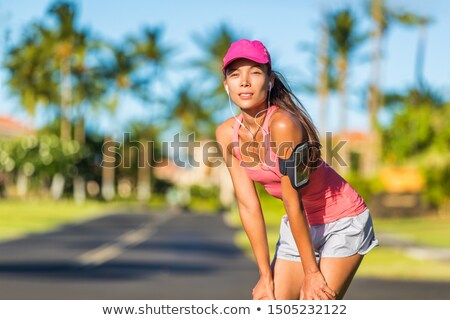 Tired runner woman running with sports cap and sport armband with earphones listening to mobile musi Stock photo © Maridav