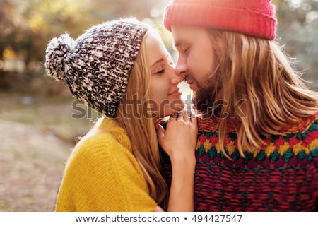 Happy young girlfriend and boyfriend wears sweater and warm socks, sit close to each other on white  Stock photo © vkstudio