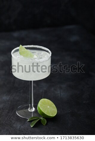 Classic glass of Margarita cocktail with fresh limes on wooden background. Stock photo © DenisMArt