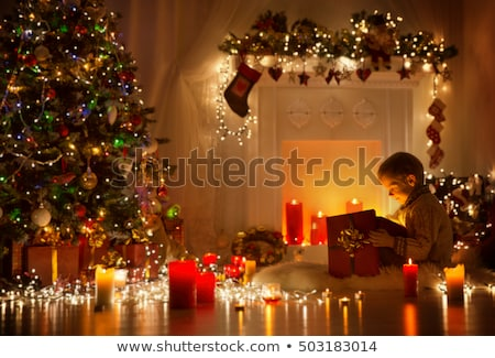 Santa sitting at the Christmas tree, fireplace and looking at ca Stock photo © HASLOO