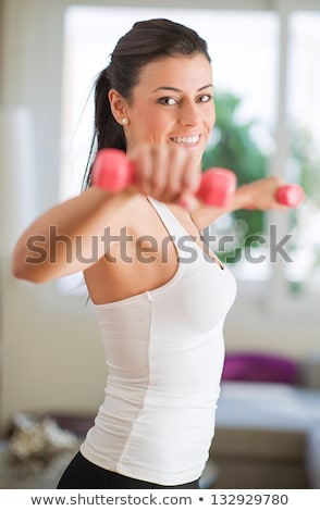 portrait of young woman exercising with dumbbell stock photo © wavebreak_media