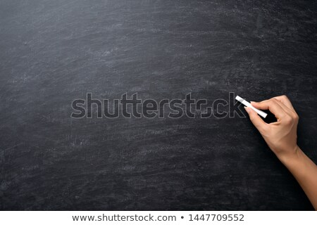 hand holding chalk over blackboard Stock photo © vkraskouski