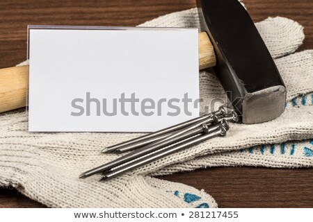 Hammer with nails and badge on protective gloves Stock photo © cherezoff