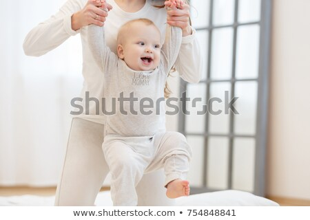 baby with diaper learning to walk with help of his mother isolated with large copy space for your m stock photo © zurijeta