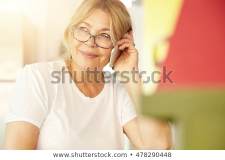 smiling blonde woman talking on phone stock photo © deandrobot