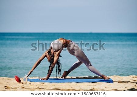 Full length of woman exercising on mat at beach stock photo © wavebreak_media