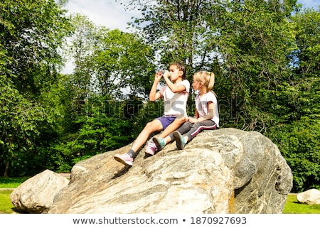 Friends sitting together on boulder Stock photo © IS2