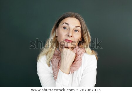 Suspicious senior woman with hand on chin Stock photo © IS2